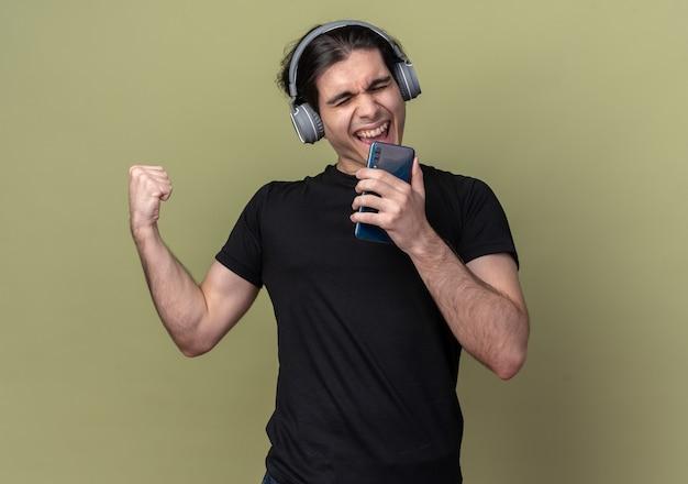 Podekscytowany, z zamkniętymi oczami, młody przystojny facet ubrany w czarną koszulkę i słuchawki, trzymając telefon i śpiewa na białym tle na oliwkowej ścianie