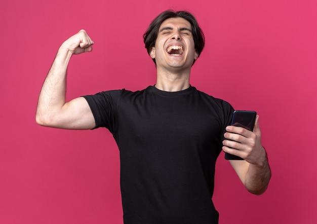 Podekscytowany z zamkniętymi oczami młody przystojny facet ubrany w czarną koszulkę trzymając telefon pokazujący tak gest na białym tle na różowej ścianie