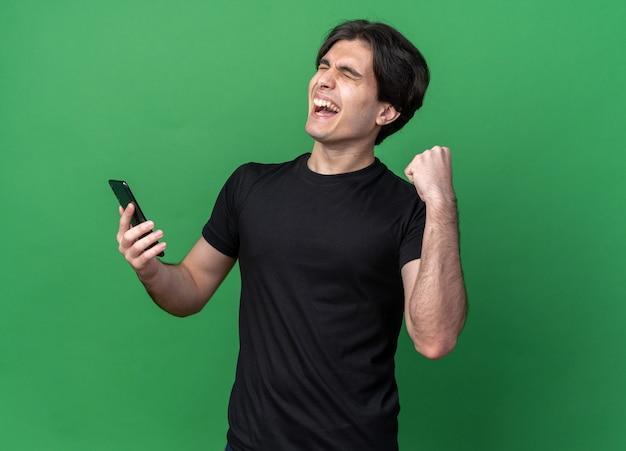 Podekscytowany z zamkniętymi oczami młody przystojny facet ubrany w czarną koszulkę trzymając telefon pokazujący tak gest na białym tle na zielonej ścianie