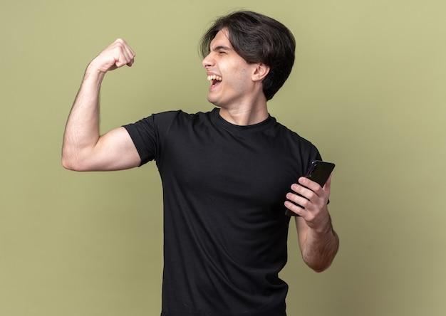 Podekscytowany z zamkniętymi oczami młody przystojny facet ubrany w czarną koszulkę trzymając telefon robi silny gest odizolowany na oliwkowej ścianie