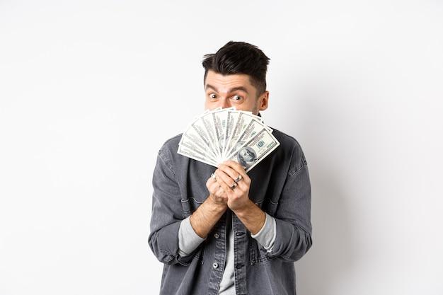 Podekscytowany zabawny facet ukrywa twarz za dolarowe i uśmiecha się, pokazując pieniądze w gotówce, stojąc na białym tle.