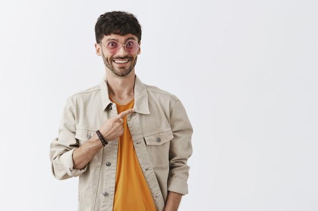 Podekscytowany zaintrygowany przystojny facet w okularach przeciwsłonecznych pozujący przy białej ścianie