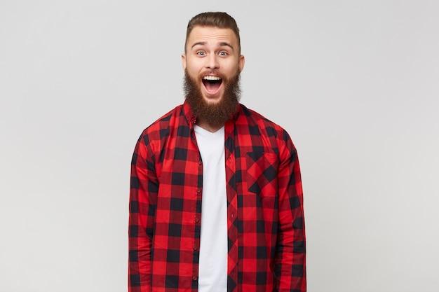 Podekscytowany, zaskoczony, atrakcyjny młody brodaty facet w kraciastej koszuli, otworzył usta z powodu zdumienia, z fryzurą wąsów fasion, na białym tle