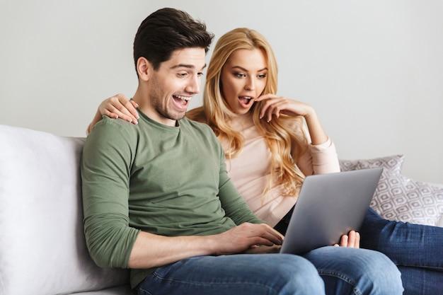 Podekscytowany zaskoczony młoda para kochających za pomocą laptopa.