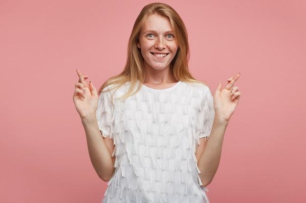 Podenerwowana młoda radosna ruda kobieta z naturalnym makijażem podnosząca ręce ze skrzyżowanymi palcami i patrząc podekscytowana na aparat z szerokim, wesołym uśmiechem, stojąca na różowym tle