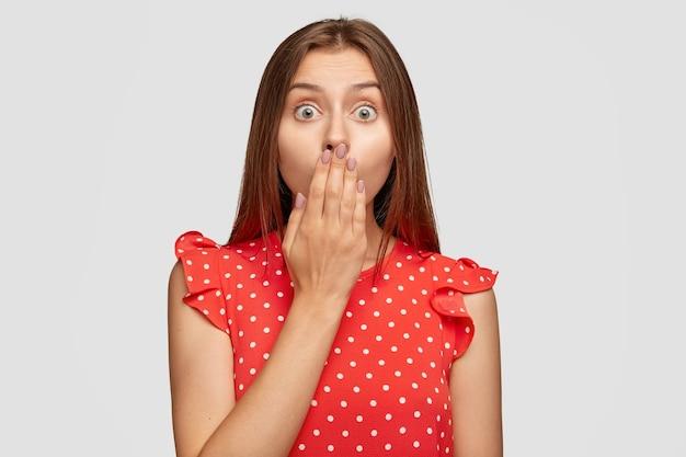 Podenerwowana, zszokowana kobieta z czerwoną szminką pozuje na białej ścianie
