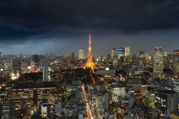 Podeszczowa burza nad tokio miastem, japonia w nocy z chmurzący nad tokio wierza w japan.