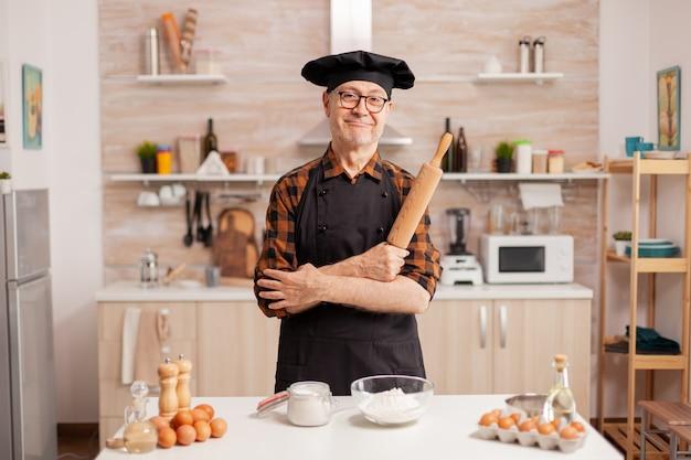 Podeszłym wieku człowiek ubrany szef kuchni bonete uśmiechający się w domowej kuchni. emerytowany piekarz w mundurze kuchennym przygotowuje składniki ciasta na drewnianym stole gotowy do gotowania domowego smacznego chleba, ciast i makaronów