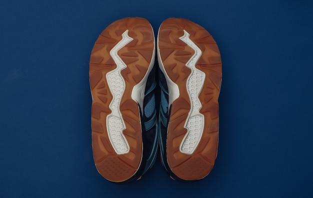 Podeszwa butów do biegania na klasycznym niebieskim tle. zdrowy styl życia, trening fitness. kolor 2020. widok z góry