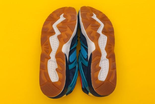 Podeszwa buty sportowe (trampki) na żółtym tle. zdrowy tryb życia. widok z góry