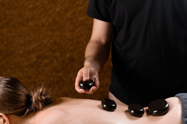 Podgrzewane kamienie na plecach kobiety. masaż kamieniami w spa dla relaksu.