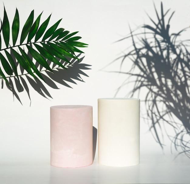 Podium butelek kosmetycznych i zielony liść z cieniem na białym tle