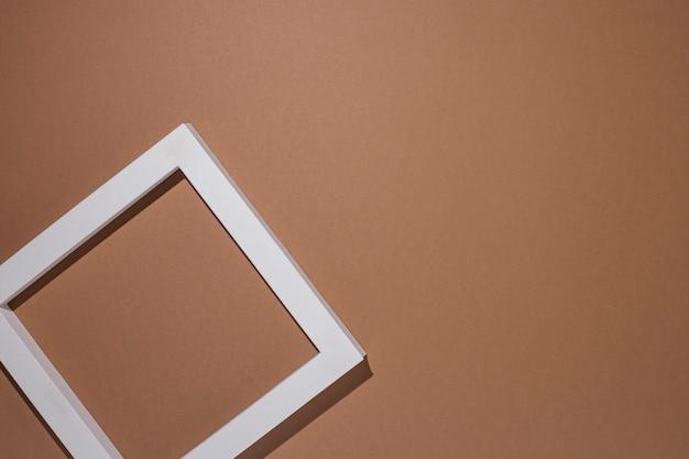 Podium do prezentacji kwadratowa biała ramka na brązowym tle. widok z góry, układ płaski.