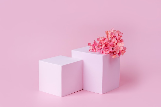Podium o geometrycznych kształtach do ekspozycji produktów. monochromatyczna platforma z kwiatami na różowym tle