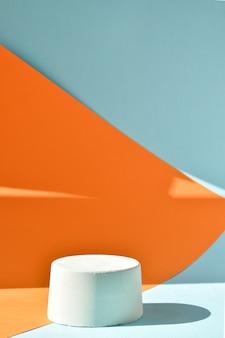 Podium to pomarańczowo-niebieskie tło z figurą geometryczną wykonaną z betonu. scena z gablotą wykonaną z cementu. minimalistyczne tło. prezentacja kosmetyków.