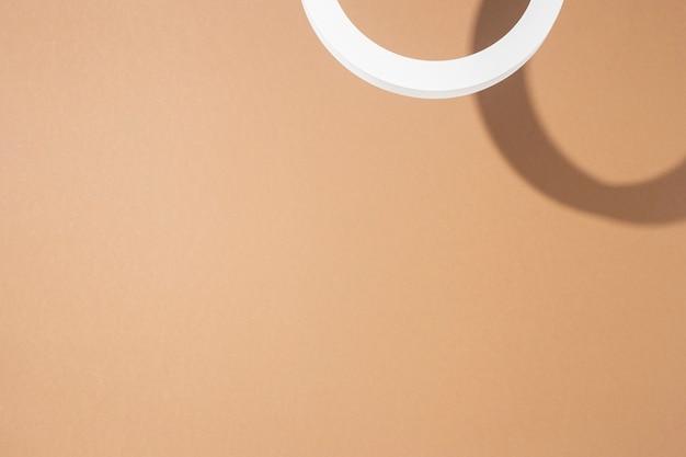 Podium z białym kółkiem do prezentacji na jasnobrązowym tle. widok z góry, układ płaski.