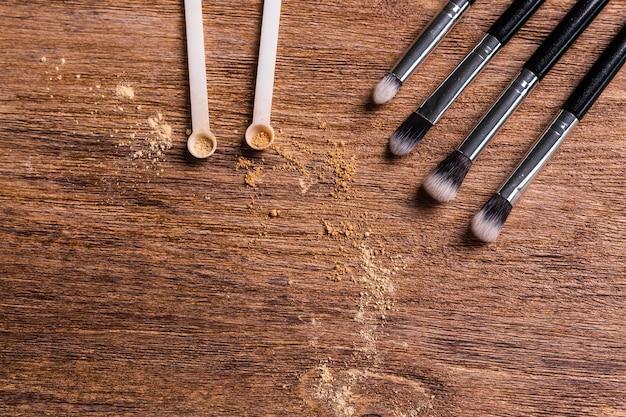 Podkład mineralny w proszku z pędzlami na drewnianym tle z miejscem na kopię. ekologiczne i organiczne produkty kosmetyczne