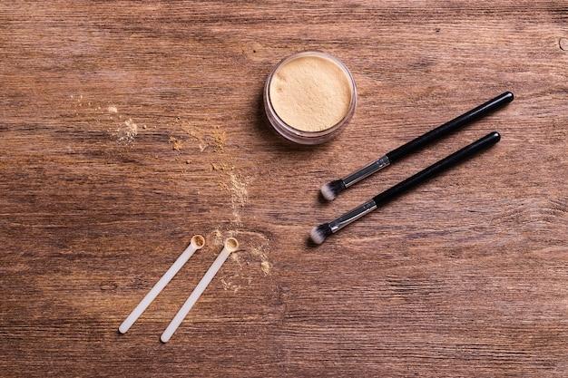 Podkład mineralny w pudrze z pędzlami na drewnianym tle. ekologiczne i organiczne produkty kosmetyczne