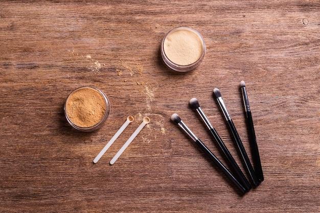 Podkład mineralny w pudrze z pędzlami na drewnianym tle ekologiczny i organiczny piękno