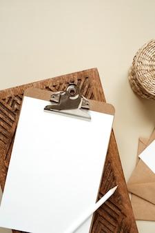 Podkładka do schowka na tablet z pustym arkuszem papieru na beżowym stole. widok z góry na płasko