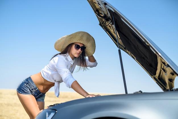 Podkreślił, młoda kobieta, patrząc na silnik swojego samochodu. problemy z podróżą. samochód wymaga naprawy.