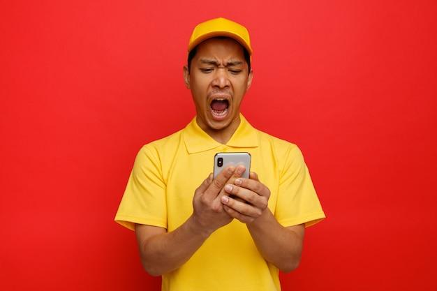 Podkreślił, młody człowiek noszenie czapki i munduru, trzymając i patrząc na krzyczący telefon komórkowy
