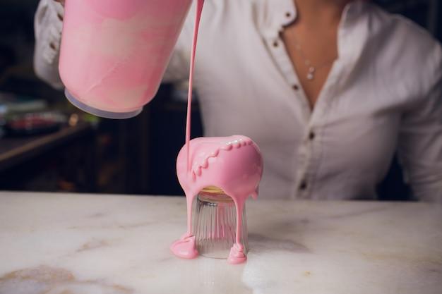 Podlewanie glazury, cukiernik wytwarza słodycze, ciasto ma podobny kształt serca