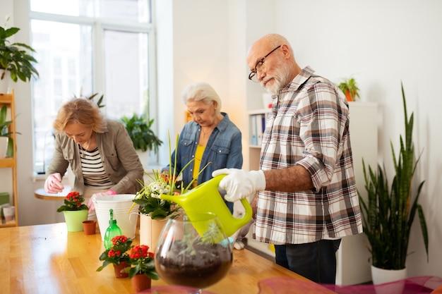 Podlewanie kwiatów. przyjemny starszy mężczyzna trzymający konewkę podczas podlewania kwiatów