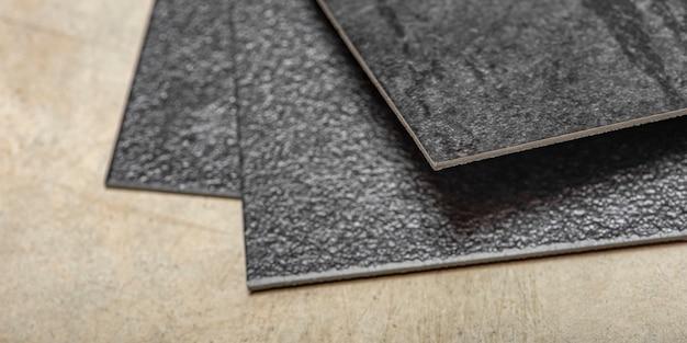 Podłoga winylowa pcv. tekstura podłogi winylowej jest czarna. próbki wykładziny winylowej, czarne płytki pcv na posadzce betonowej przed montażem.