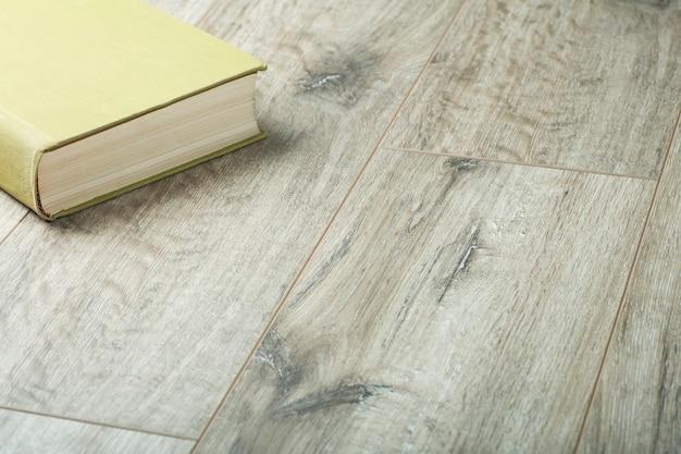 Podłoże laminowane. książka na podłodze. drewniany laminat i deski parkietowe na podłogę w aranżacji wnętrz.