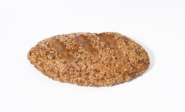 Podłużny chleb wypiekany z mąki żytniej z białym sezamem i nasionami lnu na białym tle