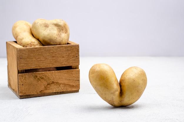 Podły ziemniaki o różnych kształtach w drewnianym pudełku, miejsce.