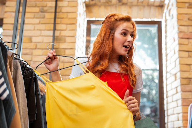 Podniecenie. emocjonalna młoda dziewczyna trzymająca jasnożółtą bluzkę i czująca wrażenie, patrząc na nowe ubrania w modnym sklepie