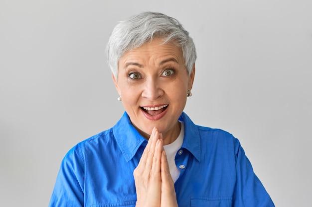 Podniecenie, szok, zaskoczenie i pozytywna reakcja. emocjonalna ekstatyczna radość kaukaska kobieta w niebieskiej koszuli szeroko otwierająca usta, podekscytowana spontaniczną podróżą, trzymająca się za ręce