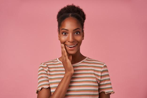 Podniecona młoda atrakcyjna, kręcona brunetka kobieta trzyma podniesioną dłoń na policzku, patrząc zaskoczony z przodu, stojąc nad różową ścianą