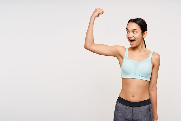 Podniecona młoda ładna brunetka szczupła kobieta z fryzurą w kucyk, z otwartymi ustami, pokazująca silny biceps, odizolowana na białej ścianie