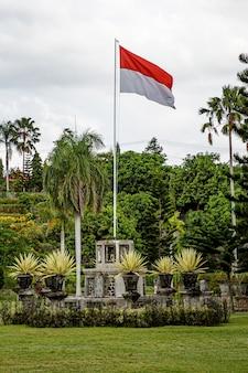 Podniesiona flaga indonezji w parku na świeżym powietrzu.