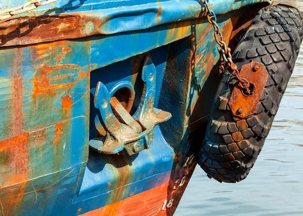 Podniesiona kotwica na pokładzie starego zardzewiałego statku
