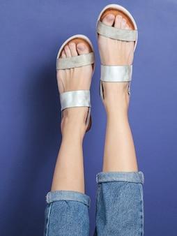 Podniesione kobiece nogi w niebieskich dżinsach i modnych skórzanych sandałach