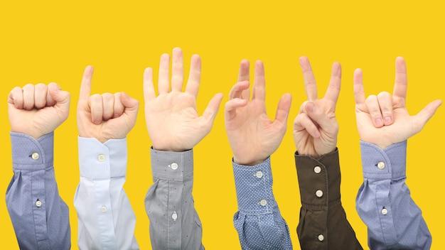 Podniesione ręce różnych mężczyzn na żółtej powierzchni. pokazywanie znaków palców w celu wyrażenia emocji.