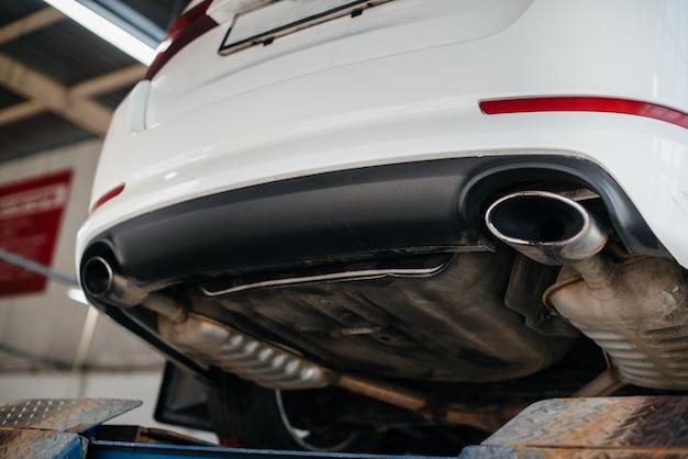 Podniesiony samochód na windzie na stacji paliw w celu zdiagnozowania układu wydechowego. stacja serwisowa
