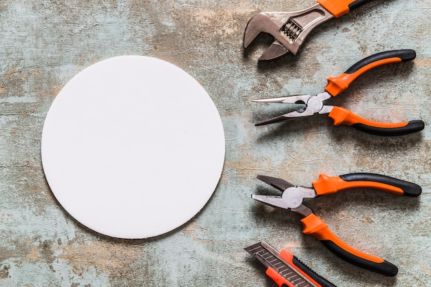 Podniesiony widok białej okrągłej ramy oprócz różnych stołów roboczych