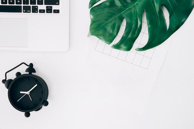 Podniesiony widok czarnego budzika; laptop; strona i zielony liść potwora na białym biurku