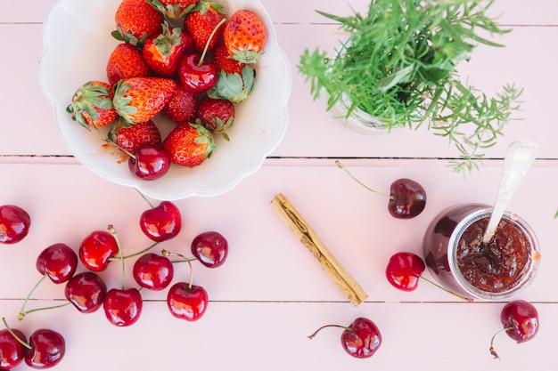 Podniesiony widok dżemu; wiśnie i rozmaryn w pobliżu świeżych truskawek w misce