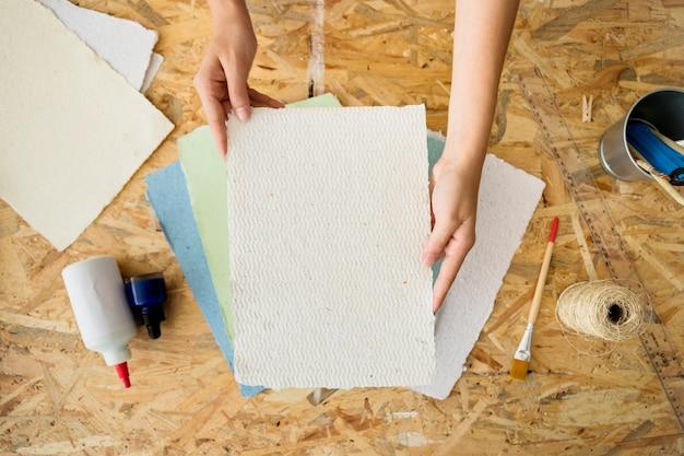 Podniesiony widok kobiecej ręki trzymającej papier czerpany