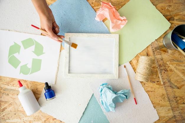 Podniesiony widok kobiety ręka maluje białą farbę na foremce