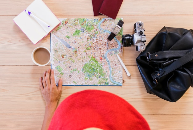 Podniesiony widok kobiety ręka z podróżniczymi akcesoriami i filiżanką herbata na biurku