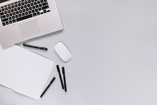 Podniesiony widok laptopa; mysz; notatnik i długopis na szarym tle