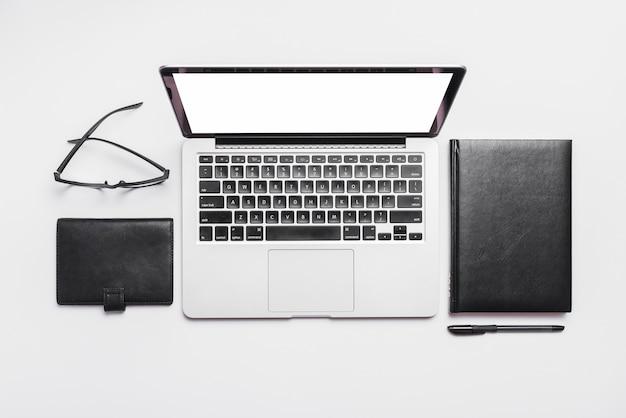 Podniesiony widok laptopa; okulary i pamiętniki na białym tle