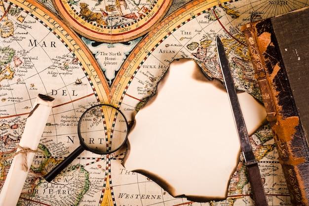 Podniesiony widok lupy, spalonego papieru i nóż na mapie